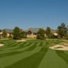 A view of the clubhouse with green protected by bunkers in foreground at Colorado Golf Club