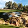 A sunny day view of a hole protected by sand traps from the Golf Club at Devils Tower
