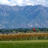 A view of a green with mountains in background at Crane Field Golf Course