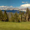 View of a green with mountains in the background from the Meadow Golf Course at Pole Creek Golf Club